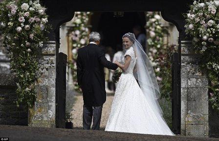 Pippa Middleton é escoltada por seu pai, Michael Middleton, como ela chega para o seu casamento com James Matthews